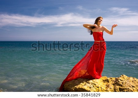 Beautiful woman in red dress at the sea beach - stock photo
