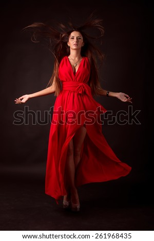 Beautiful woman in red dress. National beauty woman in a flowing red dress and hair developing on a wind. Studio photography. Harvesting concept for design. Layout for advertising.