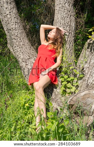 Beautiful woman in red dress relax near a tree in a park