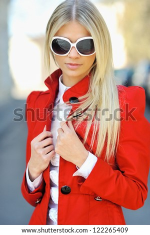 Beautiful woman in red dress wearing sunglasses in summer - stock photo
