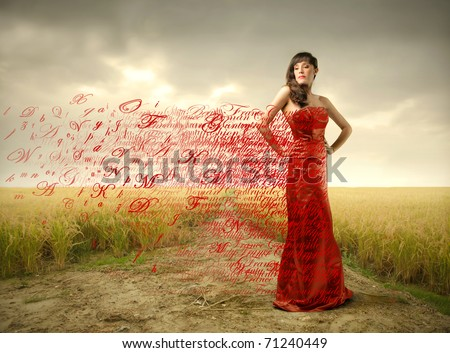 Beautiful woman in red dress with alphabet letters flying away from it - stock photo