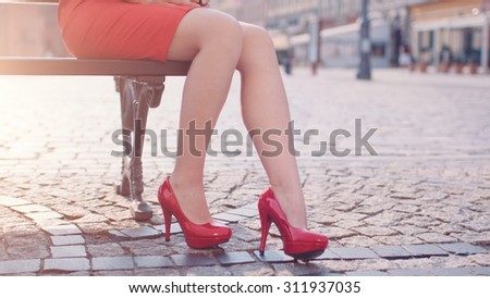Beautiful woman in red high-heeled shoes and dress enjoying sunny morning in the city. Close up on legs. Lens Flare. - stock photo