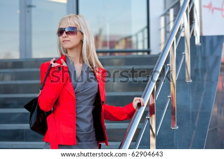 Beautiful woman in red jacket standing on the shop