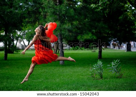 Beautiful woman in red jumping in park - stock photo