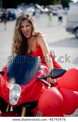 Beautiful woman in red posing on motorcycle - stock photo