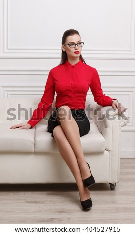 Beautiful woman in red shirt and eyeglasses sitting on a sofa - stock photo
