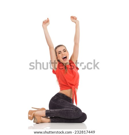 Beautiful woman in red top, black jeans and high heels sitting on the floor, shouting and rising arms. Full length studio shot isolated on white. - stock photo