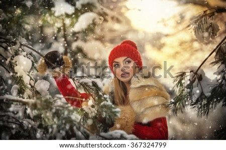 Beautiful woman in red with brown fur cape enjoying the winter scenery in forest. Blonde girl posing under snow-covered trees branches. Young female with snowflakes around in bright cold day, makeup - stock photo