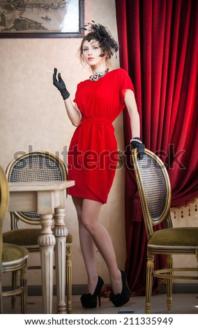 Beautiful woman in red with gloves and creative hairstyle posing near long purple  curtains. Romantic mysterious lady smoking in luxurious vintage interior. Attractive fashionable female in red.  - stock photo
