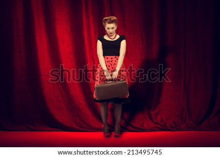 Beautiful woman in retro style is on the stage with a traveling bag on a background of red curtain. - stock photo