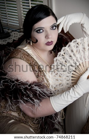 Beautiful woman in retro styled clothes and feather boa - stock photo