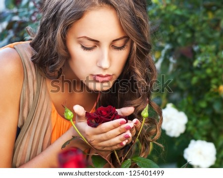 beautiful woman in roses garden - stock photo
