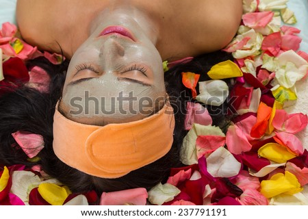 Beautiful woman in salon.Spa therapy for young woman receiving facial mask at beauty salon - indoors.Cosmetology, beautician, beautiful background - concept of a facial care.  - stock photo