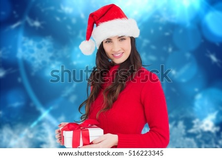 Beautiful woman in santa hat holding a christmas gift against digitally generated background