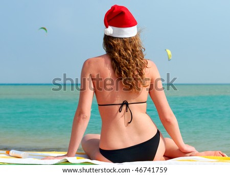 beautiful woman in santa hat looking at sea