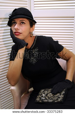Beautiful woman in sequined black dress with black hat - stock photo