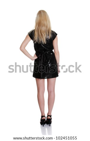 Beautiful woman in sexy black dress standing with her back against white background - stock photo