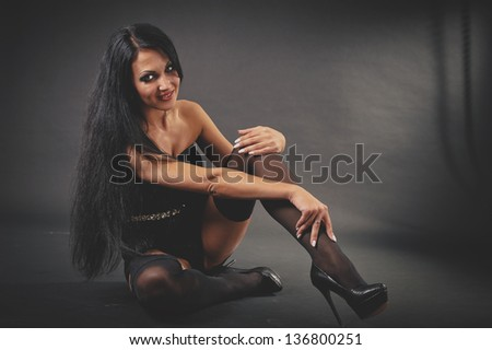 beautiful woman in sexy evening dress against dark background. Portrait of glamour beautiful young woman - black background.