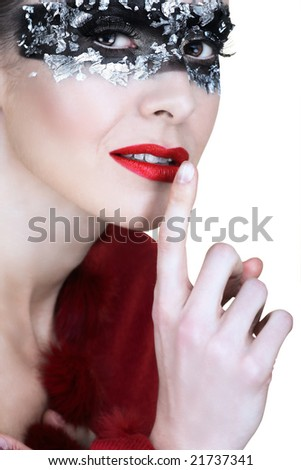 beautiful woman in silver leaf and black mask, holding finger next to her red lips - stock photo