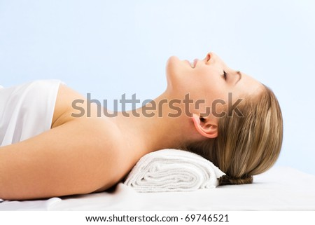 Beautiful woman in spa center on blue background - stock photo