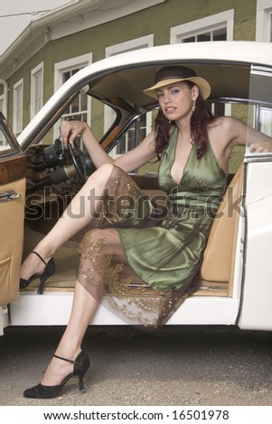 Beautiful woman in summer hat and dress stepping out of a vintage sports car. - stock photo