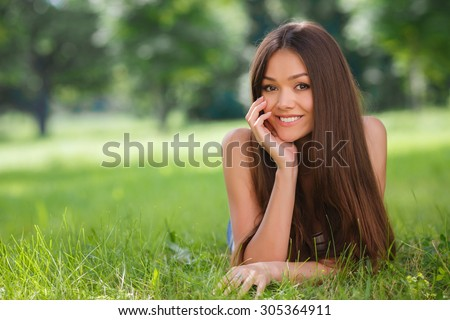 Beautiful woman in summer park. Beautiful Young Woman Outdoors. Enjoy Nature. Healthy Smiling Girl lying on Green Grass. Happiness. Freedom. Summer. Brunette happy woman in park on green lawn - stock photo
