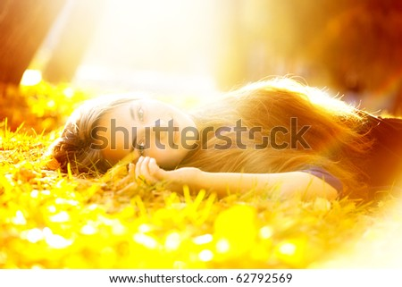 beautiful woman in sunbeam lying on the grass - stock photo