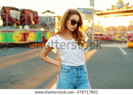 Beautiful woman in sunglasses and a white T-shirt in the park at sunset.