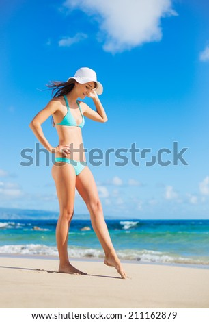 Beautiful woman in sunhat and bikini relaxing on sunny day at the beach