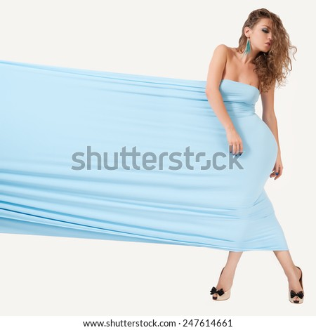 Beautiful woman in the a beautiful blue fabric. Girl posing on studio background. - stock photo