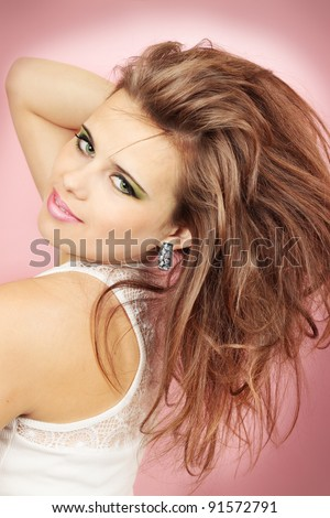 Beautiful woman in the earring against the pink background