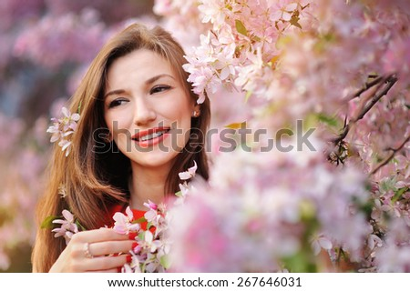 Beautiful woman in the flowering spring garden. - stock photo