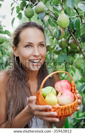 Beautiful woman in the garden with apples and pears in the crib - stock photo