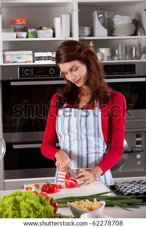 Beautiful woman in the kitchen cutting a red bellpepper - stock photo