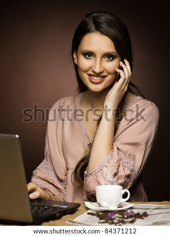 Beautiful woman   in the kitchen while working on laptop and having coffee - stock photo