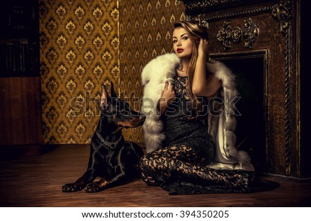 Beautiful woman in the precious jewelry and fur coat sitting by the fireplace with her dog. Classic interior. Beauty, fashion. - stock photo