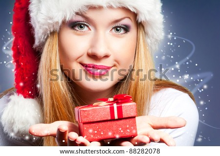 Beautiful woman in the Santa Claus hat with gift