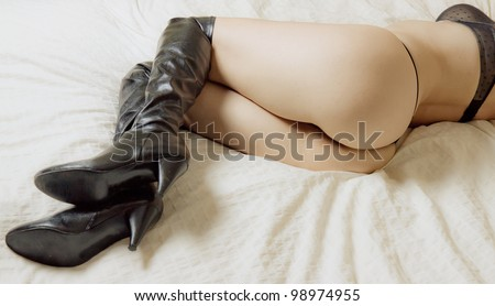 Beautiful woman in thigh high leather boots, panties and bra - stock photo