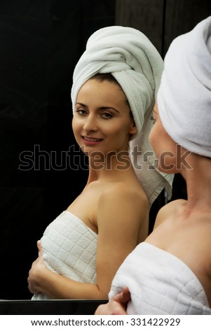 Beautiful woman in towel looking at the mirror.