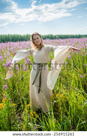Beautiful woman in traditional dress relaxes on fireweed meadow - stock photo