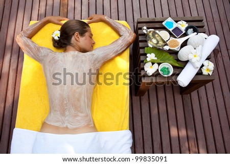 Beautiful woman in tropical spa making face mask and other treatments - stock photo