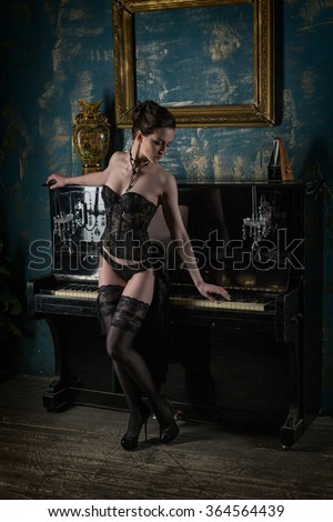 Beautiful woman in underwear near of the piano - stock photo