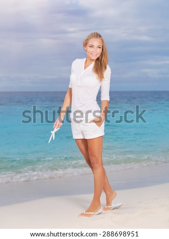 Beautiful woman in vacation, pretty blond girl walking along sandy coast with starfish in hand, enjoying summer holidays on tropical resort - stock photo