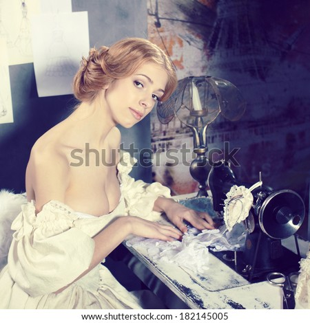 Beautiful woman in vintage dress is in clothing design studio