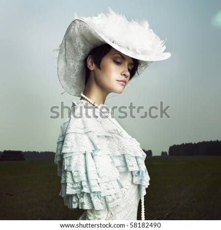 Beautiful woman in vintage dress on nature - stock photo