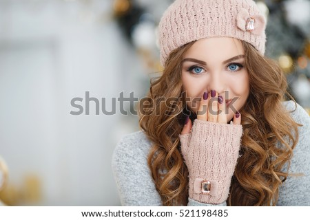 beautiful woman in warm clothing on christmas tree background. Very beautiful girl with blue eyes in a white hat costs about silver Christmas tree and smiling, close up