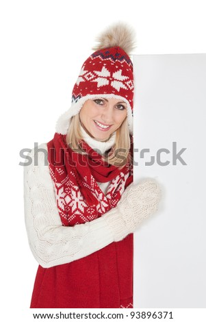 Beautiful woman in warm winter clothing presenting an empty board. Isolated on white
