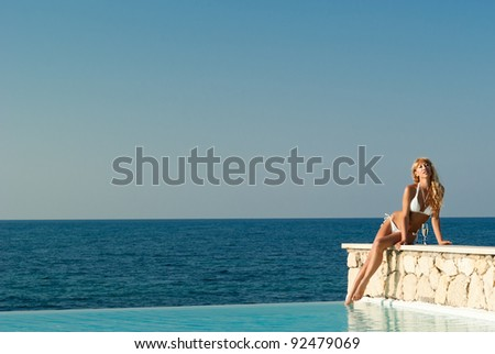 Beautiful woman in white bikini sitting on the edge of infinity pool and looking in camera. Crete. Greece - stock photo