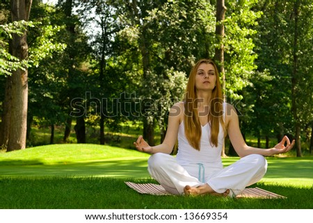Beautiful woman in white doing yoga outdoors. - stock photo