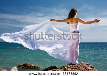 Beautiful woman in white dress at the sea beach - stock photo